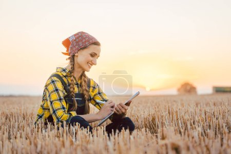 Photo for Farmer woman calculating harvest yield after a long day using pen and paper - Royalty Free Image