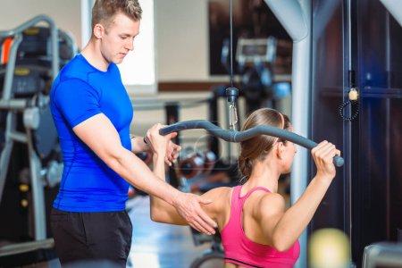 Photo pour Entraîneur personnel beau et expérimenté guidant une belle femme tout en faisant de l'exercice pour les muscles pectoraux et les épaules dans un club de fitness moderne - image libre de droit
