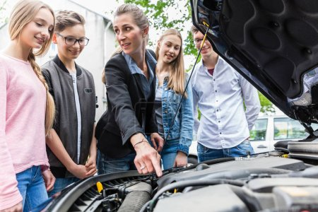 Photo for Driving teacher showing class the engine of car, letting them look under the hood - Royalty Free Image