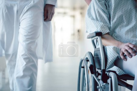 Doctor and nurse pushing wheelchair with patient in hospital