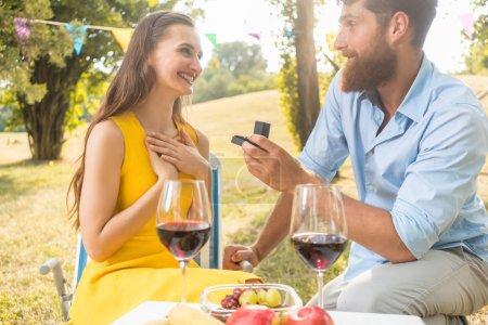 Photo pour Jeune homme beau assis sur un genou plié tout en montrant à sa belle petite amie une bague de fiançailles pendant un pique-nique romantique avec du vin rouge et des fruits frais - image libre de droit