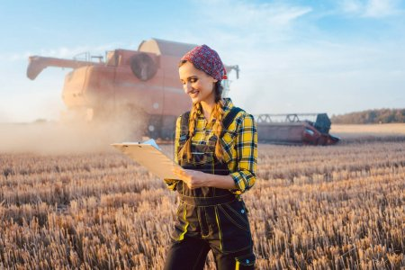 Photo for Farmer on a field during harvest with clipboard doing controlling - Royalty Free Image