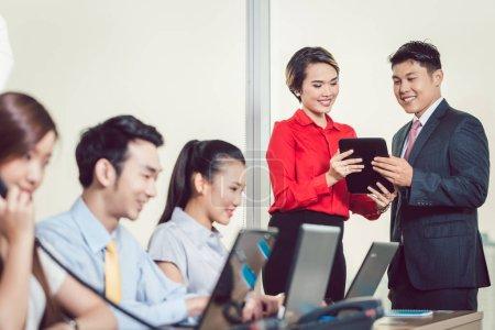 Photo pour Équipe qui travaille en face de partenaires d'affaires ayant la discussion à l'aide de tablette numérique - image libre de droit