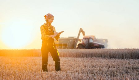 Photo for Farmer woman and combine harvester on wheat field during sunset - Royalty Free Image