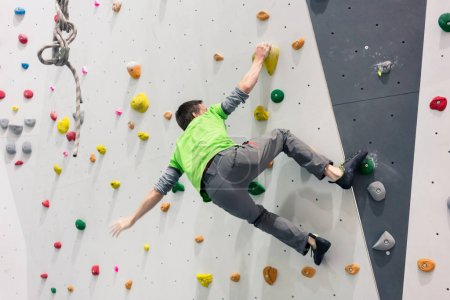 Photo for Brave athletic man climbing on wall without protection of rope - Royalty Free Image