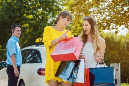 Photo pour Deux femmes se montrant leurs courses dans des sacs sortant du taxi - image libre de droit