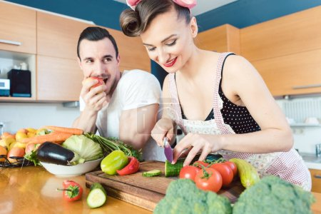 Rather lazy man Is watching his wife preparing the food