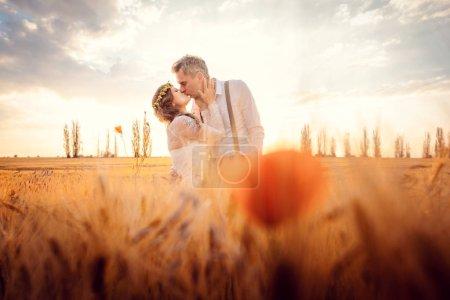 Photo pour Couple de mariage embrassant dans un cadre romantique sur un champ de blé pendant le coucher du soleil - image libre de droit