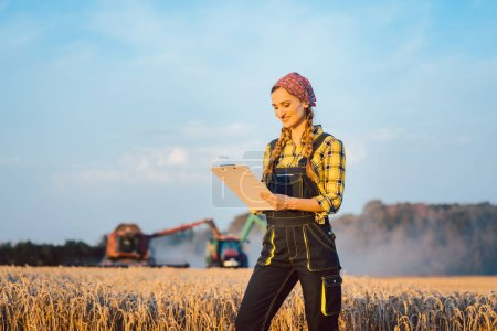 Photo for Farmer woman with clipboard on field, harvest going on, combine harvester in the background - Royalty Free Image
