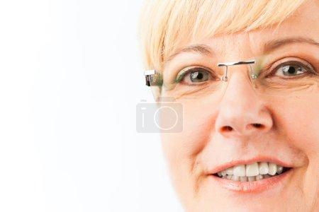 Photo pour Portrait rapproché d'une femme âgée avec un sourire en dents de dents portant des lunettes regardant la caméra - image libre de droit
