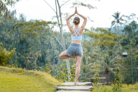 Photo pour Femme sur riz paddy en pose de yoga relaxant dans ses vacances - image libre de droit