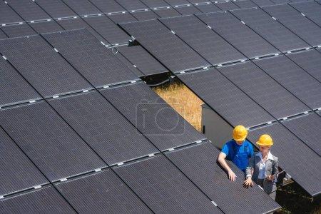 Foto de Dos personas de pie en medio de células solares en una planta de energía inspeccionando los módulos - Imagen libre de derechos