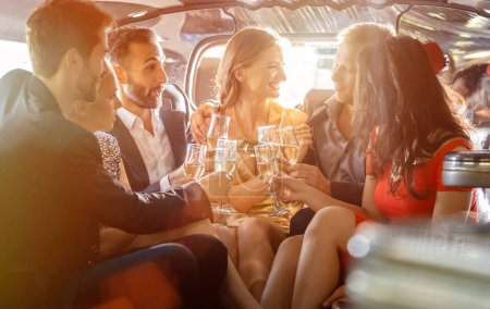 Photo for Group of women and men clinking glasses in a limousine having fun and being happy - Royalty Free Image