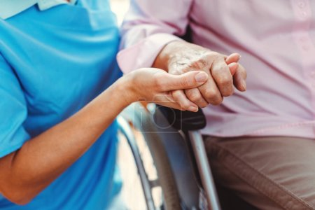 Photo for Nurse consoling a senior woman in the nursing home holding her hand in the nursing home - Royalty Free Image