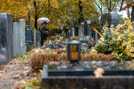 Photo pour Tombes sur le cimetière en automne avec un couple pleurant les morts debout entre les tombes - image libre de droit