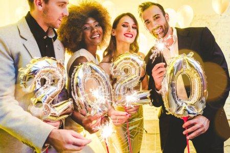 Photo pour Groupe de fêtards célébrant l'arrivée de 2020, hommes et femmes regardant à la caméra - image libre de droit