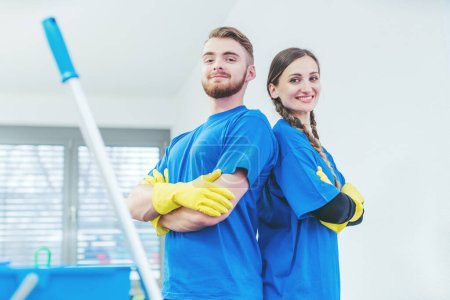 Photo for Cleaners being proud of their service standing arms folded, team of woman and man - Royalty Free Image