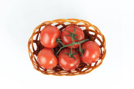 branch of ripe tomatoes in a wicker basket.isolated on white