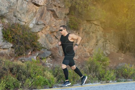 Photo for Male athlete runner while running in the mountain road - Royalty Free Image
