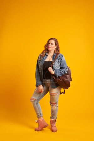 Pretty plus-size girl in casual clothes with backpack on shoulde