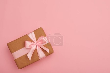 Photo for Top view of wrapped gift box with pink ribbon bow on pink flatlay - Royalty Free Image
