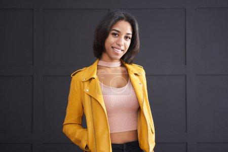 Teenage girl smiling in yellow leather jacket