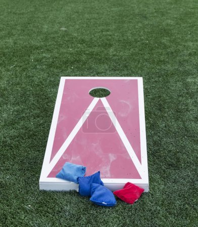 Photo for A red and white wooden cornhole game is on green turf with blue and red bean bags. - Royalty Free Image