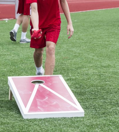 Photo for A kid is throwing a bean bag during a game of corn hole on a turf field outside. - Royalty Free Image