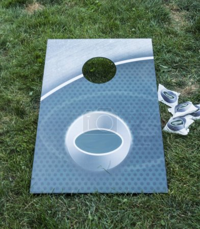 Photo for A aqua colored corn hole game is on the grass with white bean bags on the side. - Royalty Free Image