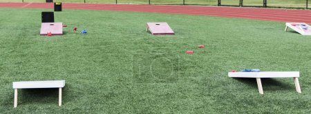 Photo for A high school gym class has wooden corn hole games set up on its turf field with bean bags for classes. - Royalty Free Image