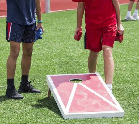 Photo for Two boys play corn hole during gym class on a green turf field in the sunshine. - Royalty Free Image