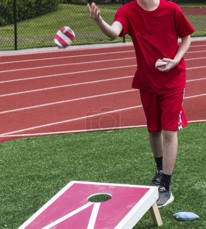 Photo for A teenage boy tosses a bean bag while playing corn hole in gym class on the turf with the track behind him. - Royalty Free Image