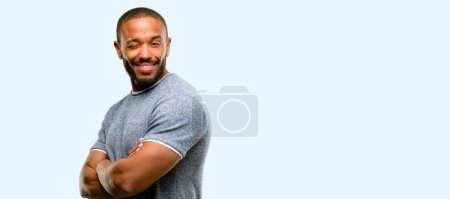 African american man with beard blinking eyes with happy gesture isolated over blue background