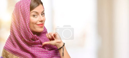 Young arab woman wearing hijab proud, excited and arrogant, pointing with victory face