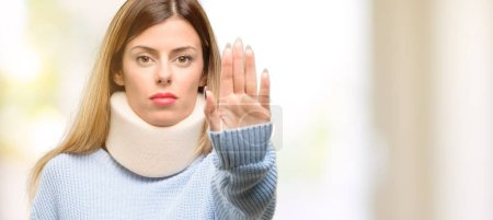 Young injured woman wearing neck brace collar annoyed with bad attitude making stop sign with hand, saying no, expressing security, defense or restriction, maybe pushing