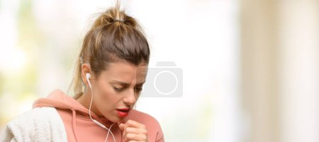 Young sport woman wearing workout sweatshirt sick and coughing, suffering asthma or bronchitis, medicine concept