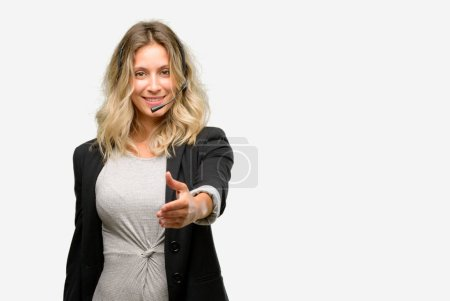 Young woman operator from call center holds hands welcoming in handshake pose, expressing trust and success concept, greeting