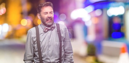 Photo for Middle age man, with beard and bow tie crying depressed full of sadness expressing sad emotion at night club - Royalty Free Image