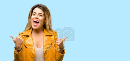 Photo for Beautiful young woman smiling broadly showing thumbs up gesture to camera, expression of like and approval - Royalty Free Image