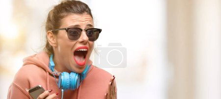 Photo for Young sport woman with headphones and sunglasses smiling broadly showing thumbs up gesture to camera, expression of like and approval - Royalty Free Image