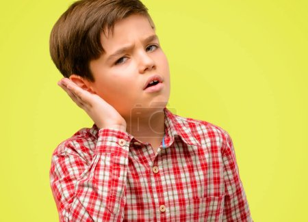 Handsome toddler child with green eyes holding hand near ear trying to listen to interesting news expressing communication concept and gossip over yellow background
