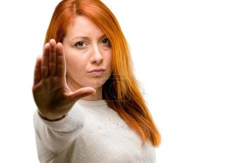 Photo pour Belle jeune femme rousse agacée avec une mauvaise attitude faisant signe d'arrêt avec la main, disant non, exprimant la sécurité, la défense ou la restriction, peut-être pousser isolé sur fond blanc - image libre de droit