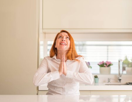 Redhead woman at kitchen begging and praying with hands together with hope expression on face very emotional and worried. Asking for forgiveness. Religion concept.
