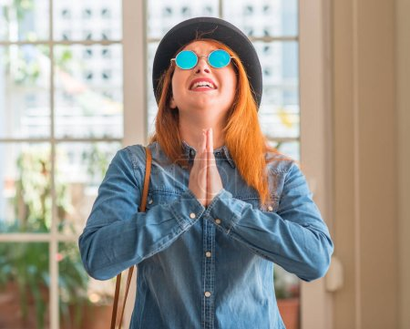 Stylish redhead woman wearing bowler hat and sunglasses begging and praying with hands together with hope expression on face very emotional and worried. Asking for forgiveness. Religion concept.