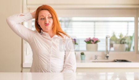 Redhead woman at kitchen confuse and wonder about question. Uncertain with doubt, thinking with hand on head. Pensive concept.