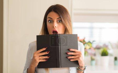 Photo pour Belle jeune femme lisant un livre choqué et émerveillé à la maison . - image libre de droit
