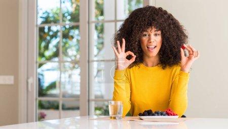 Photo pour Femme afro-américaine mangeant des framboises et des bleuets à la maison faisant signe ok avec les doigts, excellent symbole - image libre de droit