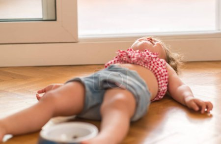 Beautiful blond child crying and shouting with tantrum laying on the floor at home.