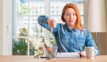 Redhead woman studying at home with angry face, negative sign showing dislike with thumbs down, rejection concept