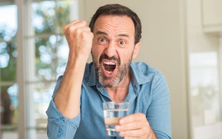 Middle age man drinking a glass of water annoyed and frustrated shouting with anger, crazy and yelling with raised hand, anger concept